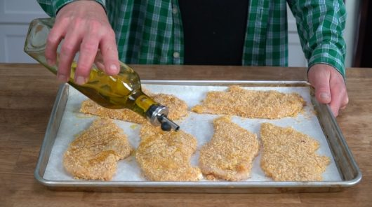 drizzle cutlets with olive oil for Crispy Baked Chicken Parmesan
