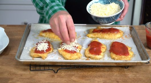 top cutlets with shredded mozzarella for Crispy Baked Chicken Parmesan